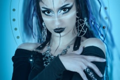 Image title : Gigi. A fantasy portrait  of a young woman held in blue tones. The woman are wearing black and white face paint and makeup. her clothes are black and she has long black hair with purple stands in it.All made with Adobe Photoshop . Images and textures provided by Caroline Julia Moore.